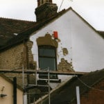 A wall with loose render due to penetrating damp