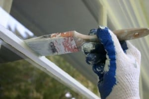 Hand holding paint brush painting a window