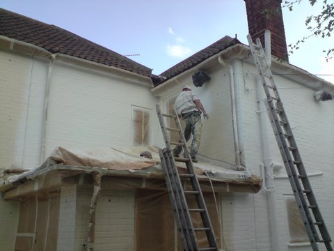 Our man spraying the exterior wall coating onto the house