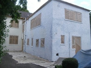 a house masked up and primed for spray coatings