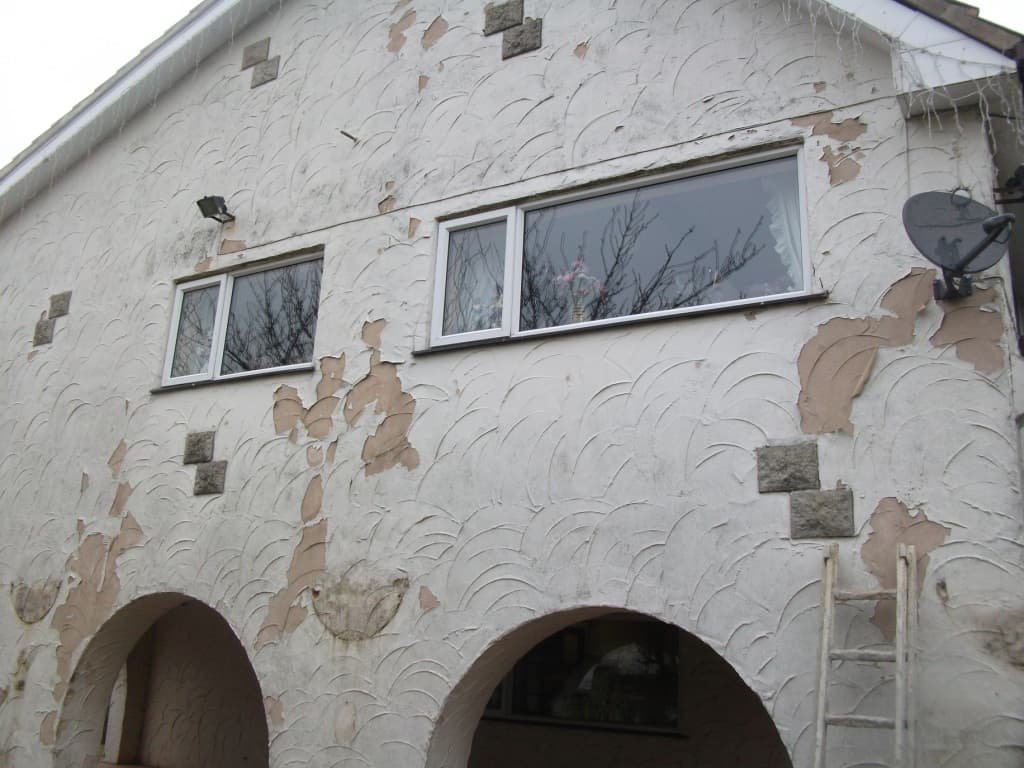 Flaking paint on a scored render home