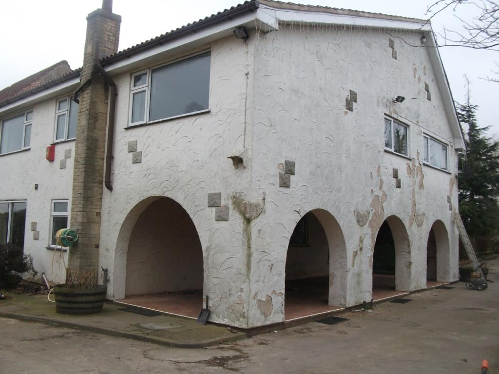 A rendered house with extensive flaking paint