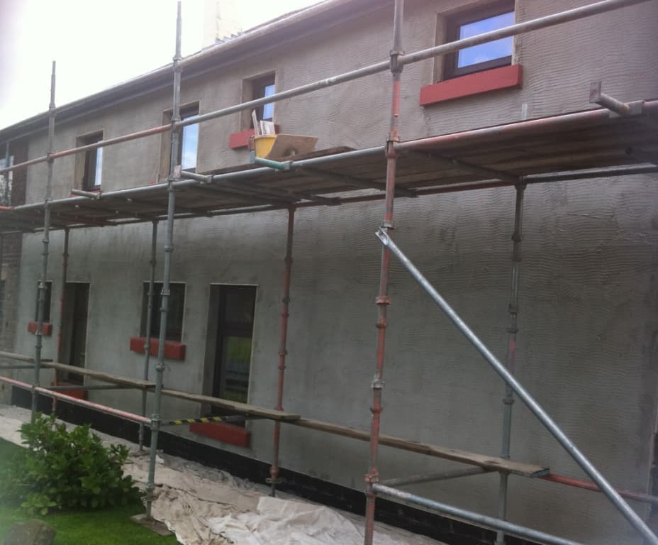 The completed scratch coat of render applied to the house