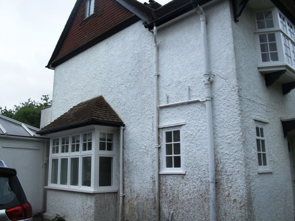 Pebbledashed house with mould on the walls and loose paint