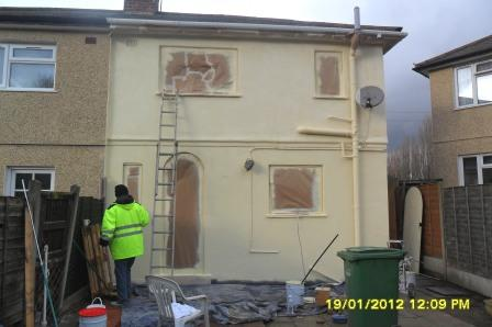 Spraying an exterior wall coating to the house