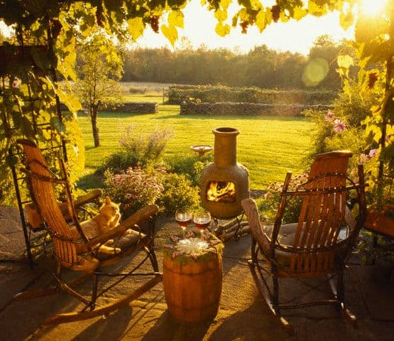 A nice view of a garden with rocking chairs