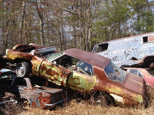 rusting cars in a field