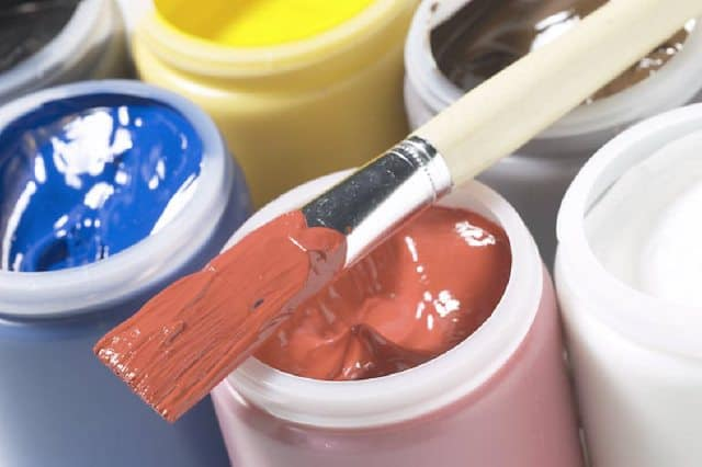 Paintbrush resting on brown bottle of paint