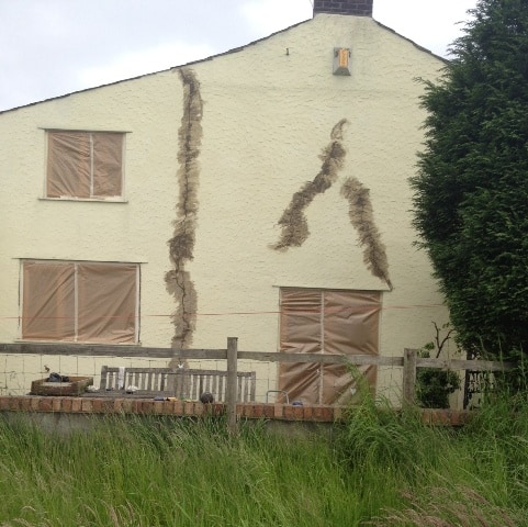 The side of house showing cracks