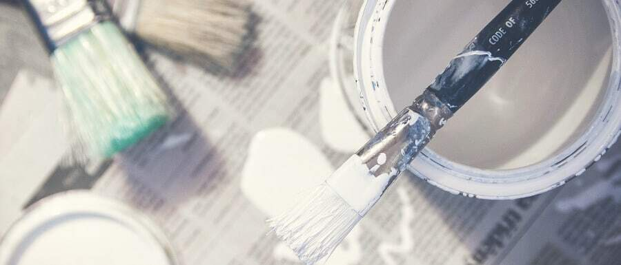 DIY paint tins and paint brushes on newspaper