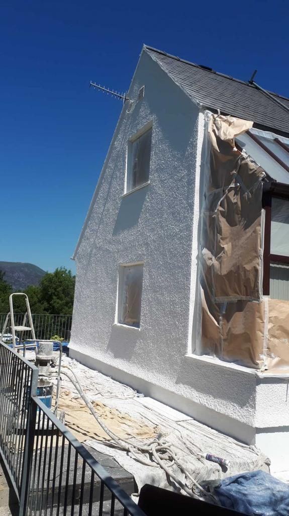 Gable end wall being sprayed with exterior wall coating-min