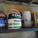 Old tins of paint on a dusty shelf