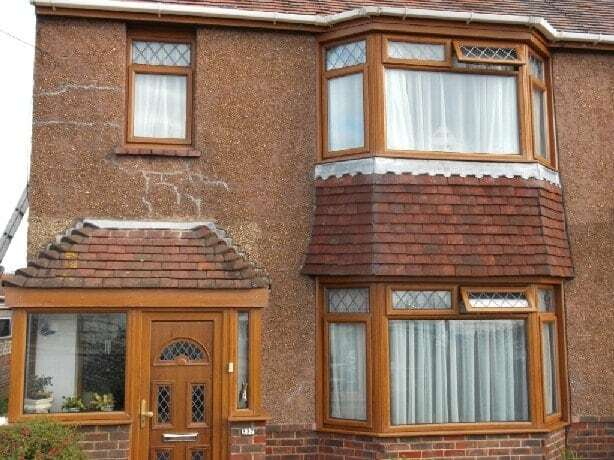 A rendered and pebbledashed house in dire need of repair showing extensive cracked rendering and loose or missing areas of pebbledash