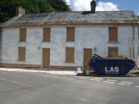 This image shows a house masked up and a coat of weatherproof primer