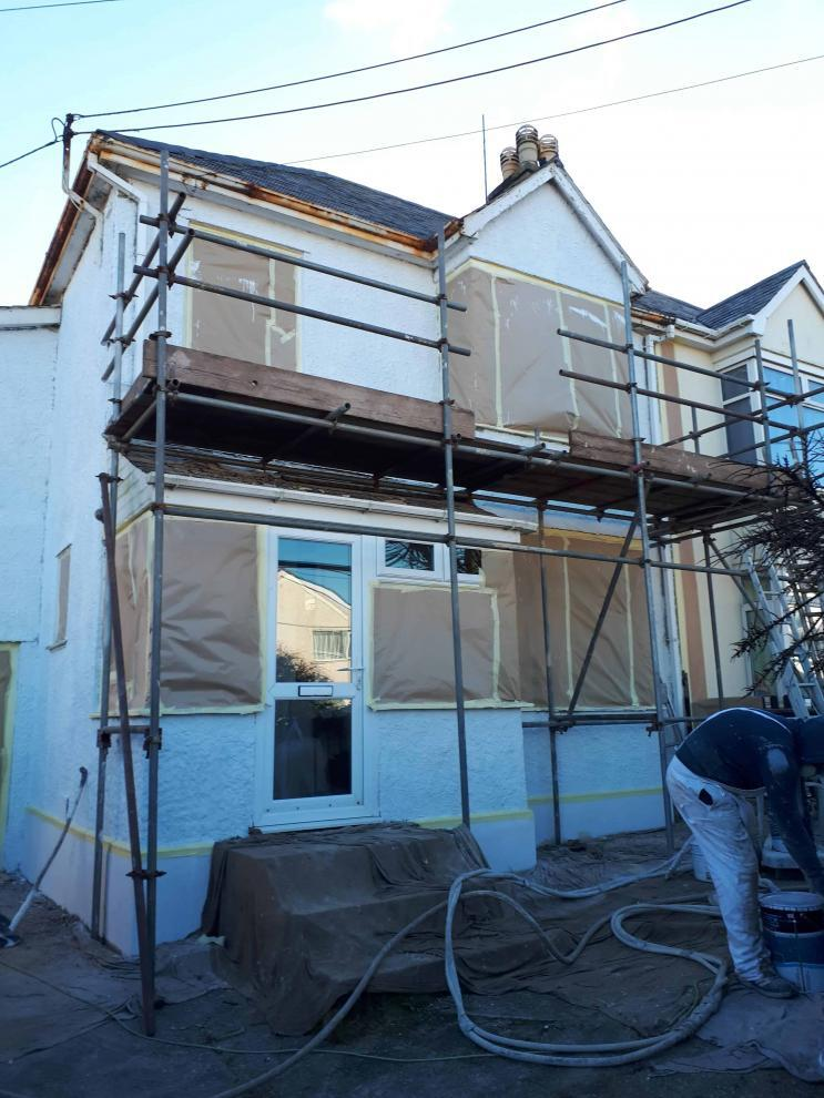 front of house in Cornwall with primer ready to have a wall coating sprayed