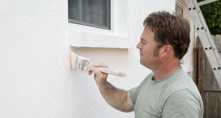 man painting exterior brick walls
