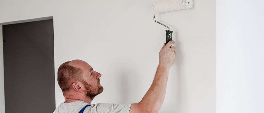 semi professional painter using trade paint on a wall